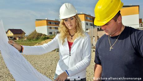 Mulher e homem trabalhando em construção
