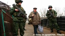 Pro-Russian rebels guard a checkpoint in Stanytsia Luhanska, Lugansk region, on March 7, 2017, as an elderly man carrying bags passes into Ukraine-controlled territory. Russia hit back March 7 at claims it is sponsoring terrorism in war-torn eastern Ukraine, dismissing as neither factual, nor legal, Kiev's contention that it is breaking its treaties by supporting pro-Moscow rebels. / AFP PHOTO / Aleksey FILIPPOV (Photo credit should read ALEKSEY FILIPPOV/AFP/Getty Images)
