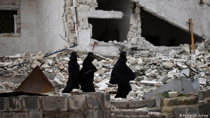 Mulheres de niqab caminham em meio à destruição no norte da Síria