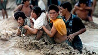 Drei Männer helfen einer Frau, einen über die Ufer getretenen Fluss zu überqueren (pixel)