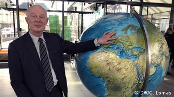 Ханс Йоахим Шельнхубер у глобуса в фойе Deutsche Welle