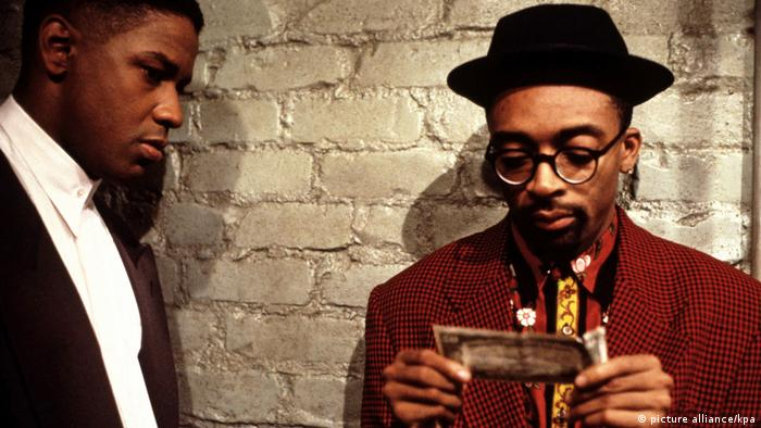 Film still from Mo' Better Blues with Denzel Washington and Spike Lee, who is holding a money bill.