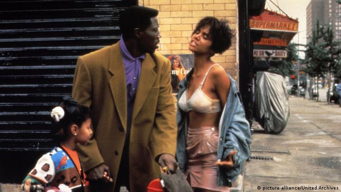 Film still 'Jungle Fever': a child, Wesley Snipes and Halle Berry, revealing her bra on a New York street.
