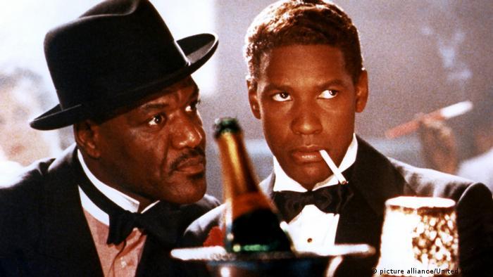 Film still 'Malcolm X': Al Freeman and Denzel Washington wearing elegant suits, smoking.