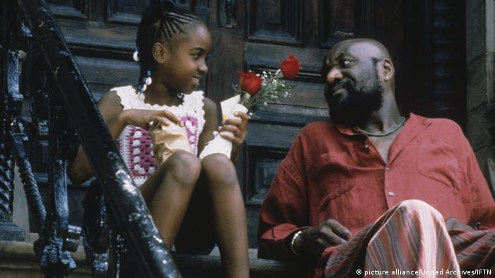 Film still 'Crooklyn' a child holding flowers, sitting on a porch with an older man.