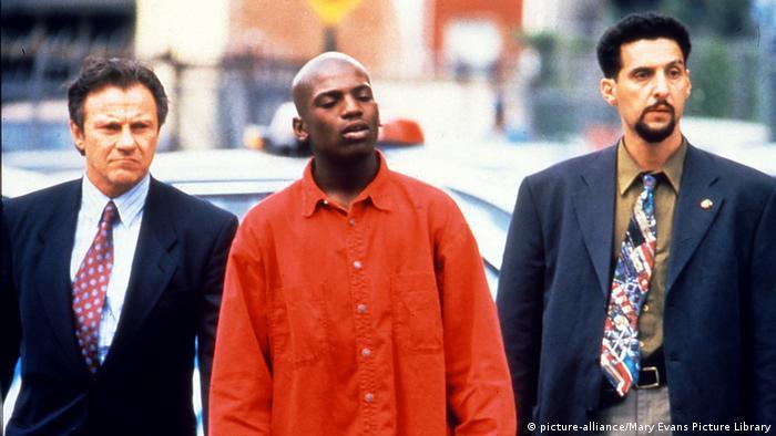 Film still 'Clockers': Harvey Keitel and John Torturro wearing a tie and jacket, Mekhi Phifer in an orange jail suit.