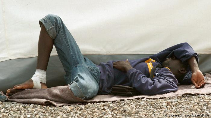 A Sub-Saharan would-be immigrant rests on the ground