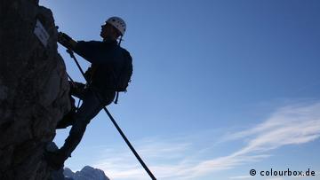 Ein Mann in Bergsteigerausrüstung klettert eine Steilwand hoch
