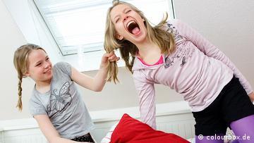 Ein Mädchen zieht ein älteres Mädchen schmerzhaft an den Haaren