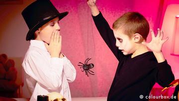 Ein Mädchen hält sich die Hände vor den Mund, ein Junge hält eine Plastik-Spinne hoch