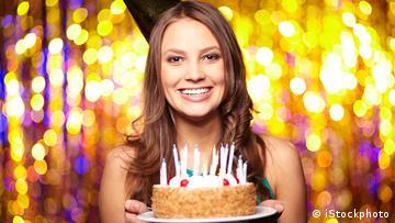 Eine Frau hält einen Geburtstagskuchen in der Hand und lächelt in die Kamera