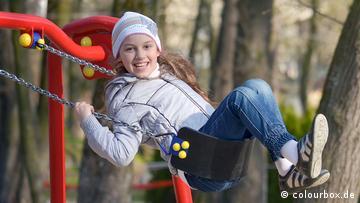 Ein Mädchen schwingt lachend auf einer Schaukel