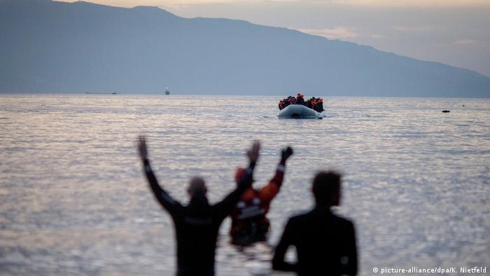 Emergency aid workers hail a boat carrying migrants