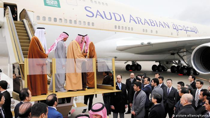 Saudi Arabia's King Salman bin Abdulaziz (2nd from R) uses an escalator to board a plane at Tokyo's Haneda airport on March 15, 2017, departing for China after a four-day visit to Japan.