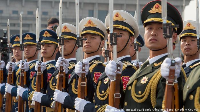Chinese soldiers are seen as Saudi Arabia's King Salman bin Abdulaziz Al Saud (L) is being welcomed by Yang Jiechi