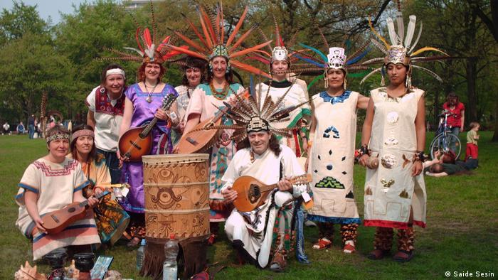 Grupo de danza prehispánica mexicana con trajes e instrumentos típicos.