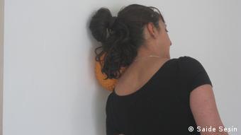 Un mujer se recarga contra una pared sosteniendo una pelota entre la cabeza y el hombro.