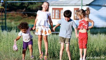 Vier Kinder stehen auf einer Wiese und halten sich an den Händen