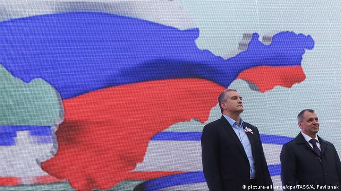 Russian-backed Crimean officials participate in a celebration marking the 3rd anniversary of Moscow's annexation of Crimea