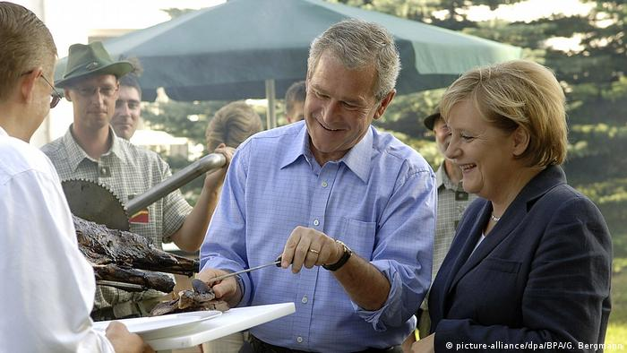 George W. Bush cutting off a piece of meat for a smiling Merkel (picture-alliance/dpa/BPA/G. Bergmann)