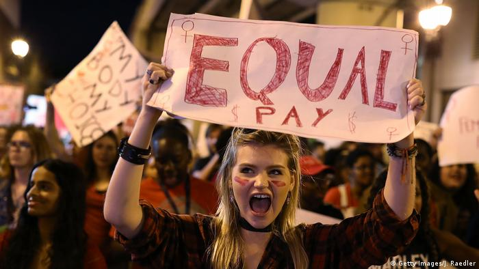 A woman holds a sign reading 'equal pay' at a march for women's rights in Miami