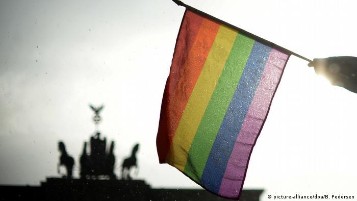 Rainbow flag against backdrop of Brandenburg Gate