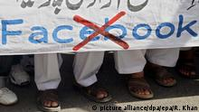 Pakistani men hold a banner during a protest against the international social networking website Facebook in Karachi Pakistan (picture alliance/dpa/epa/R. Khan)