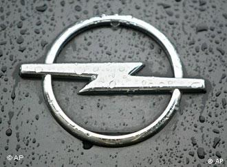 The Opel logo, seen on a car bonnet, splashed by rain