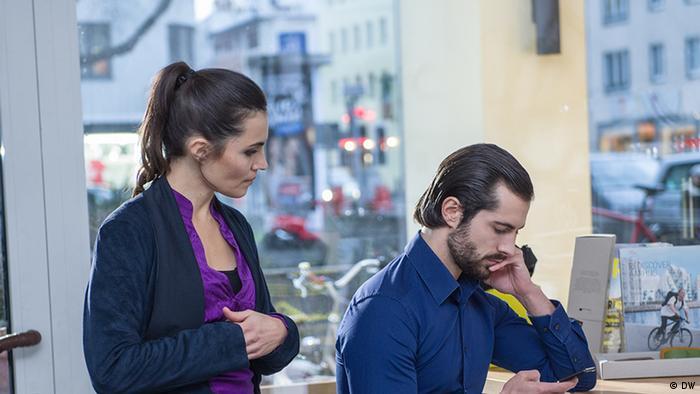 Eine Frau und ein Mann sehen sich etwas auf dem Smartphone an.