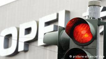 Opel factory and logo behind a red traffic light