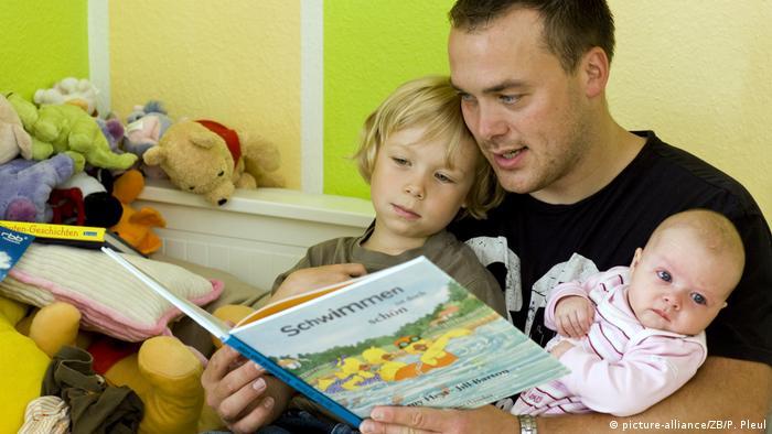 Папа, взявший родительский отпуск, читает своим детям книгу