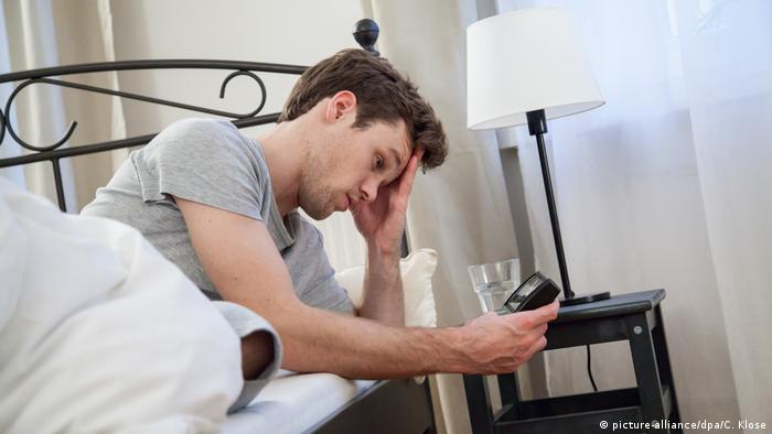 Ein junger Mann im Bett schaut müde auf seinen Wecker (picture-alliance/dpa/C. Klose)
