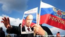 18.03.2017 A person waves a Russian national flag and a portrait of Russian President Vladimir Putin as they celebrate the third anniversary of the annexation of the Crimea by the Russian Federation in Sevastopol on March 18, 2017. / AFP PHOTO / Max Vetrov (Photo credit should read MAX VETROV/AFP/Getty Images)