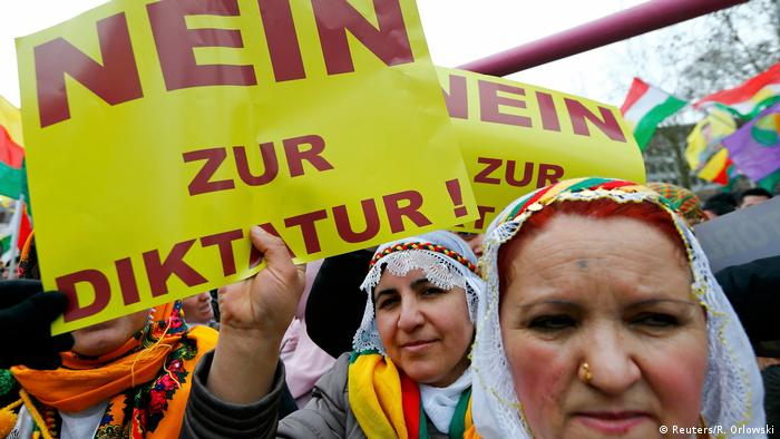 People hold placards with the slogan No to dictatorship during a demonstration organized by Kurds, in Frankfurt, March 18, 2017.