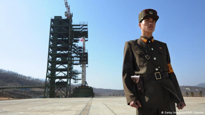 A North Korean solider stands guard in front of a rocket at the Sohae Satellite Launch Station.