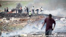 Men standing on a rubbish dump, fires burn around them and black smoke fills the air