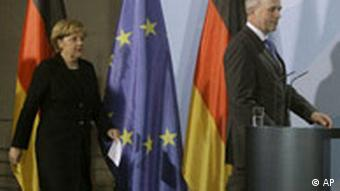 Chancellor Merkel walks to podium in front of German flag