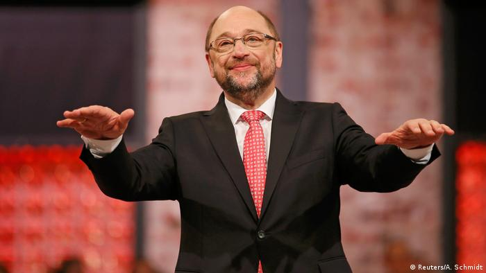 SPD candidate Martin Schulz extends his stands forward palms down while addressing an audience