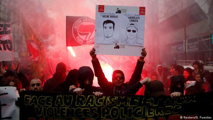 Демонстранты несут транспаранты, флаги и жгут фаеры на демонстрации в Париже