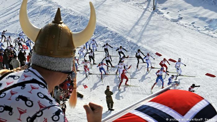 Homem com chapéu de viking olha para esquiadores