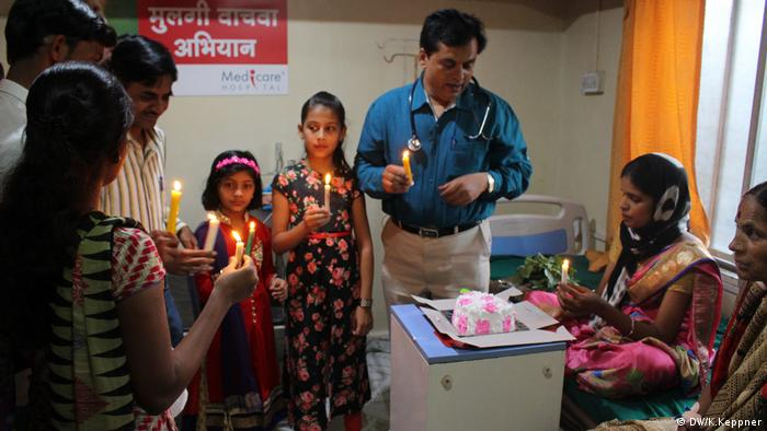 Dr Rakh, hospital staff and family members hold candles as they celebrate the birth of a girl