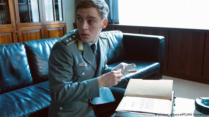 Szene aus Deutschland 83. Martin Rauch (gespielt von Jonas Nay) schaut anglsich zur Seite, während er eien Kamera über Dokumente hält (picture alliance/RTL/Nik Konietzny)