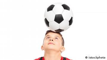 Ein Junge balanciert einen Fußball auf seinem Kopf