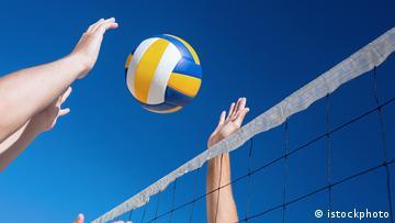 Ein Volleyball wird über Netz gespielt