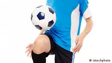 Ein Fußballspieler, der den Ball mit seinem Knie hochkickt