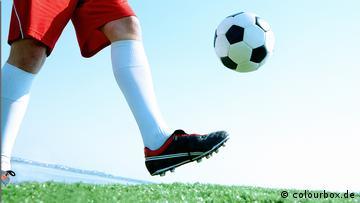Ein Fußballspieler kickt einen Ball in die Luft