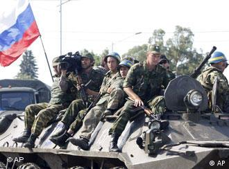 Russian soldiers with a Russian flag sit atop a tank