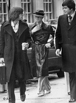 British rocker David Bowie walks toward the courthouse with his business manager and lawyer, neither identified, in Rochester, N.Y., March 25, 1976, to answer a charge of criminal possession of illegal drugs