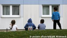 Refugee children in front of refugee home