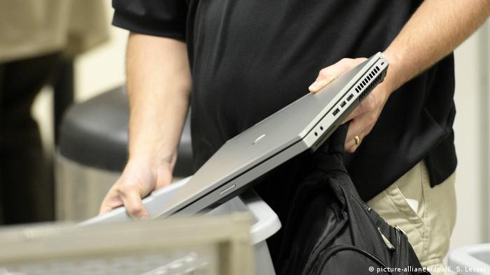 Foto simbólica de una persona con una laptop en las manos en un aeropuerto.